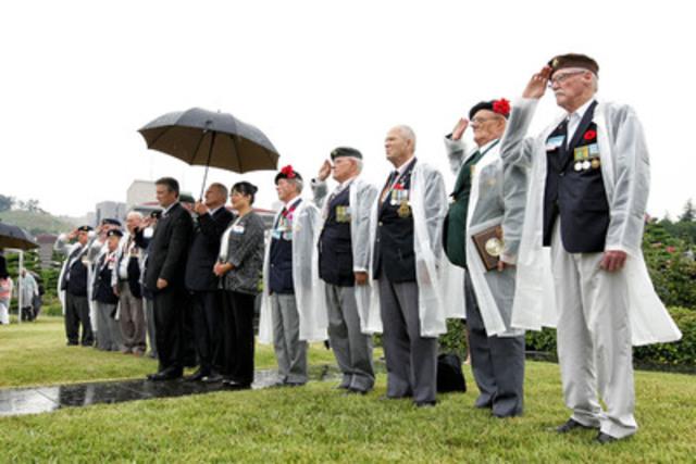 Des vétérans canadiens saluent lors de l'interprétation de la Dernière sonnerie à l'emplacement du monument canadien au Cimetière commémoratif des Nations Unies à Pusan, en République de Corée. (Groupe CNW/Anciens Combattants Canada)