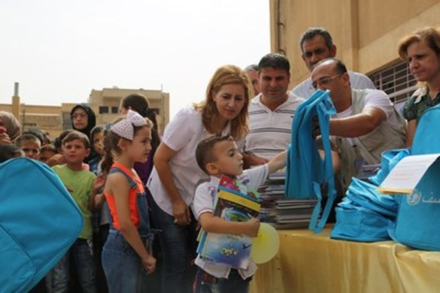 With today's announcement, the Government of Canada has made funding education a continued priority in its response to the crisis in Syria. As part of its package of support, Canada will be funding the distribution of UNICEF self-learning kits, seen here being distributed by UNICEF Representative in Syria, Hanna Singer, and UNICEF staff. (C) UNICEF/UNI198149/Soulieman (CNW Group/UNICEF Canada)