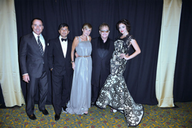 Sir Elton John and Fashion Cares Chair David Furnish are joined by Moji and Kirsten Korhani of KORHANI Home and their custom creation designed for Fashion Cares 25: A Night of Glitter and Light. To help raise additional funds for the AIDS Committee of Toronto, The Korhanis are donating $1 for every photo re-tweet @KORHANIHome. (CNW Group/KORHANI Home)