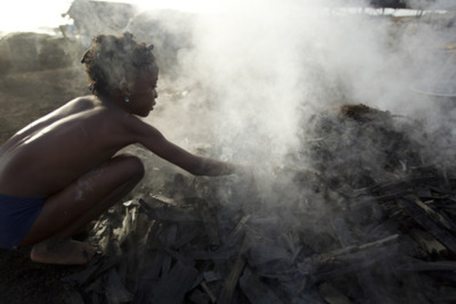 © UNICEF/UNI129897/Asselin A girl sifts hot charcoal with her bare hands, at a wood charcoal production ...