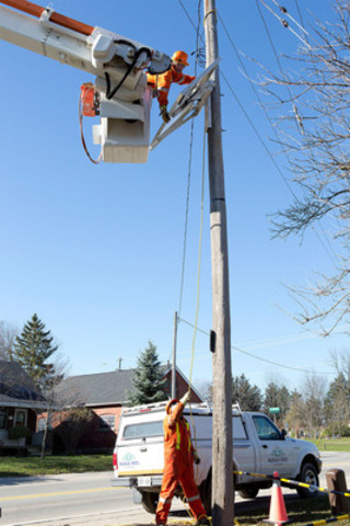 Halton Hills Hydro power line technicians Matt Stephens, on the ground, and Hessel Faber, above, install a new solar-smart grid panel on Trafalgar Road in Ballinafad. (CNW Group/Halton Hills Hydro)