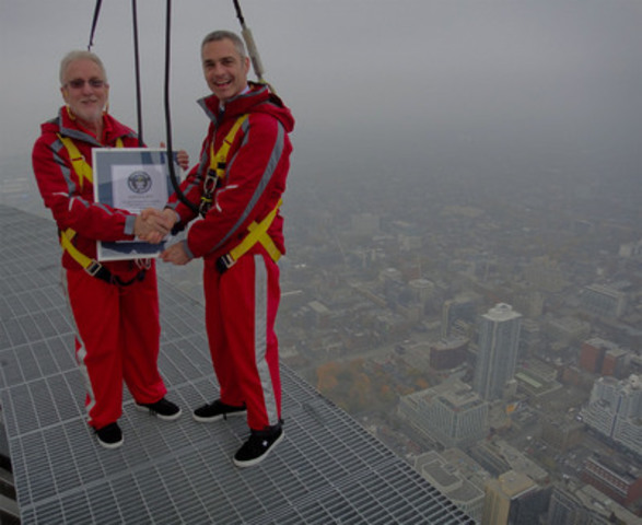 """On November 8, 2011 EdgeWalk at the CN Tower was presented with the Guinness World Record for the """"Highest External Walk on a Building"""". Carey Low, the Guinness World Records® Canadian Representative, presented the certificate to Jack Robinson, Chief Operating Officer of the CN Tower on the EdgeWalk itself, 356m/1,168ft above the ground. (CNW Group/CN Tower)"""