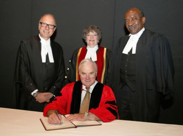 Me Peter Milliken, PC, OC signe le registre après que le Barreau lui a remis un LLD honorifique à la cérémonie d'assermentation du 22 juin à Ottawa. Derrière lui, la trésorière du Barreau Janet Minor (centre), le DG Robert Lapper, c.r. (à gauche) et le conseiller Jack Braithwaite (à droite). (Groupe CNW/Barreau du Haut-Canada)