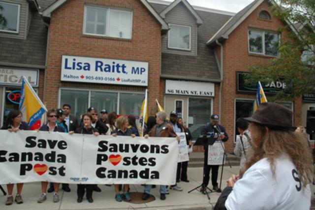 Des représentantes et représentants du Syndicat des travailleurs et travailleuses des postes (STTP) et d'autres groupes concernés manifestent devant le bureau de la ministre Lisa Raitt, à Milton. (Groupe CNW/Syndicat des travailleurs et travailleuses des postes)