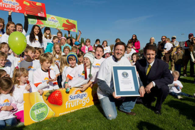 Sun-Rype CEO Dave McAnerney accepts Guinness world record for the longest fruit snack with its 300-foot long Fruit to Go, presented by Phillip Robertson, official adjudicator for Guinness World Records, amongst enthusiastic participants from the local community on October 16, 2011, in Kelowna, BC. (CNW Group/Sun-Rype Products Ltd.)