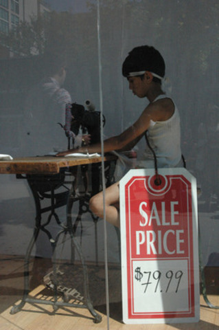 Child actor sews in Fashion Crimes storefront for #nochildforsale campaign (CNW Group/World Vision Canada)