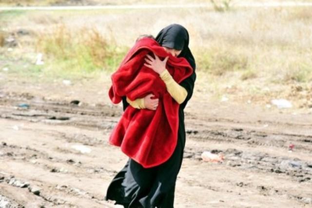 Une femme portant un enfant marche sur un chemin boueux de la ville méridionale de Preševo, à la frontière avec l'ancienne République yougoslave de Macédoine. Des milliers de personnes réfugiées et de migrantes traversent chaque jour la Serbie afin d'atteindre d'autres pays de l'Union européenne; beaucoup voyagent pendant des semaines après avoir fui le conflit. Depuis le mois de juin 2015, plus de 89 160 personnes ont franchi la frontière serbe, et l'Agence des Nations Unies pour les réfugiés estime que plus de 12 000 personnes réfugiées provenant de la Syrie et d'autres pays déchirés par la guerre se trouvent à tout moment en territoire serbe. (Groupe CNW/UNICEF Canada)