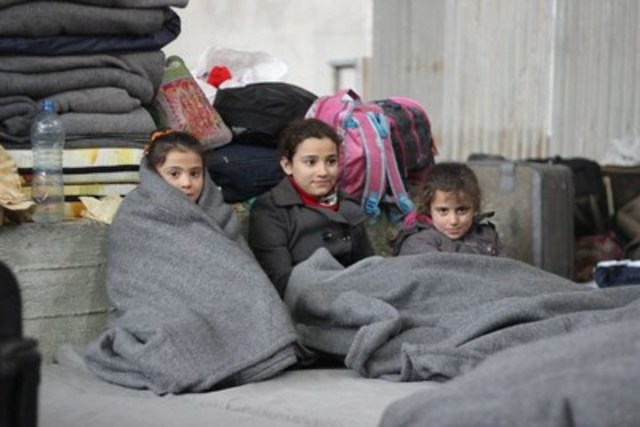 On December 1, 2016, three girls wrap themselves in blankets to keep warm at a large warehouse in Jibreen, which hosts displaced families from the recent fighting in east Aleppo. Some 31,5000 people are reported to have been displaced from and within east Aleppo since November 24, including around 19,000 children. Temperatures are dropping quickly and heavy rainfall has made conditions even worse over the past few days. UNICEF is providing blankets and winter clothing, as well as access to safe water, essential medical care, including vaccinations and psychosocial support for children. C UNICEF/UN042601/Al-Issa (CNW Group/UNICEF Canada)