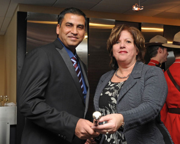 Montreal Port Authority President and Chief Executive Officer Ms. Sylvie Vachon, awarding the Gold-Headed Cane to Capt. Anuj Kararia, master of the M/V Valencia Express, the first ocean-going vessel in port in 2015. (CNW Group/Montreal Port Authority)