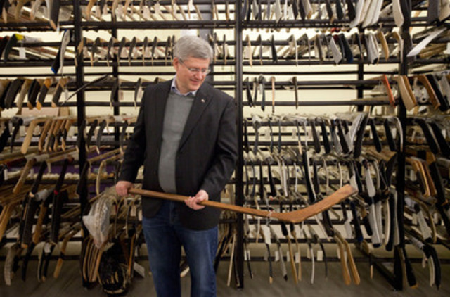 Stephen Harper holds a hockey stick from the 1907 Stanley Cup final during a research visit to the Hockey Hall of Fame in Toronto, Canada, December 2011. (CNW Group/Simon and Schuster Canada)