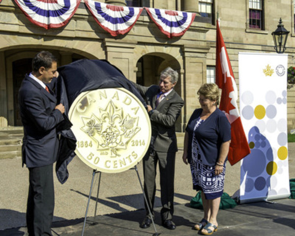 From left to right: Prince Edward Island Premier Robert Ghiz, Royal Canadian Mint CFO Marc Brûlé and Canada's Minister of Fisheries and Oceans Gail Shea, unveil a gold collector coin commemorating the 150th anniversary of the Charlottetown and Québec conferences at Province House in Charlottetown, P.E.I. on August 26, 2014. (CNW Group/Royal Canadian Mint)