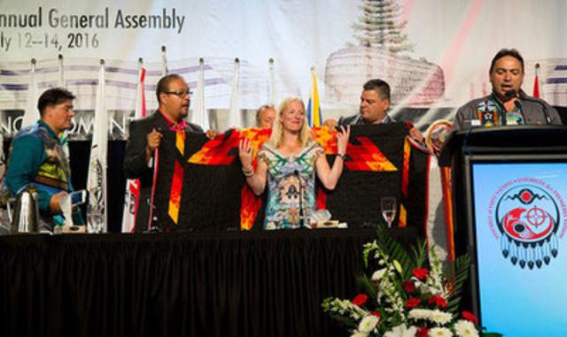 Des dirigeants autochtones drapent la ministre McKenna d'une couverture au cours de la 37e assemblée générale de l'Assemblée des Premières Nations, à Niagara Falls, le 13 juillet 2016. (Groupe CNW/Environnement et Changement climatique Canada)
