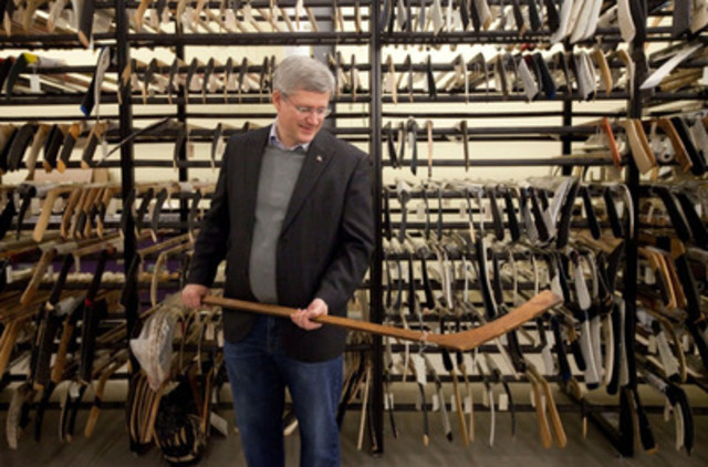 Stephen Harper holds a hockey stick from the 1907 Stanley Cup final during a research visit to the Hockey Hall of Fame in Toronto, Canada, December 2011 (CNW Group/Simon and Schuster Canada)