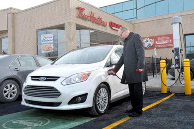 Sur cette photo, datée du 11 février, un automobiliste recharge un C-MAX Energi hybride rechargeable de Ford à un Tim Hortons d'Oakville, en Ontario, après le lancement, par la chaîne, d'un projet pilote de bornes de recharge pour véhicules électriques. (Groupe CNW/Tim Hortons Inc.)