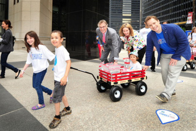 """Students including Hannah Alper and Kai Nevins lead a wagon caravan of pennies down Bay Street, accompanied by Gord Nixon, president and CEO of RBC, Jennifer Tory, regional president, Greater Toronto Region, RBC and Free The Children Co-Founder Marc Kielburger. The Free The Children/RBC """"We Create Change"""" campaign raised $1.4 million in pennies that will provide 56,000 people in developing countries with clean water for life. (CNW Group/RBC)"""