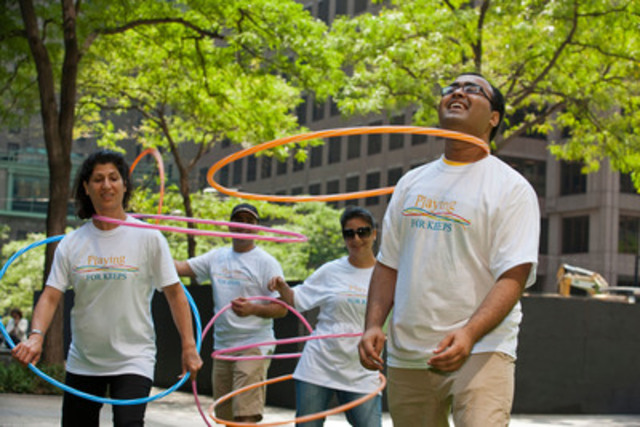 Narin (Janet) Khazaei (left) joins fellow Playing for Keeps trained Volunteer Ambassadors for a hula hoop game demonstration at the corner of King and Bay Streets to mark the launch of Playing for Keeps last summer. (CNW Group/Toronto Community Foundation)