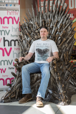 KING IN THE NORTH: Jesse Vandenbroek sits atop his newest, prized possession -- a life-size replica of the Iron Throne, from the hit HBO series Game of Thrones. The Medicine Hat resident won hmv's largest-ever Canadian competition, and claimed the throne as his own this weekend. (CNW Group/hmv Canada)