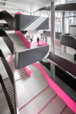 The striking multi-level Atrium at Rotman School features a serpentine staircase accented with hot pink that brightens the monochrome interior. Credit: Tom Arbun Photography Inc. (CNW Group/Kuwabara Payne McKenna Blumberg Architects)