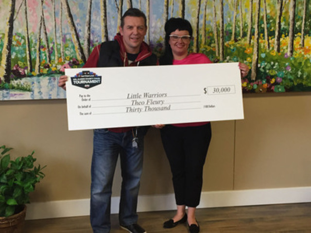 Glori Meldrum, founder and chair of Little Warriors, accepting the donation from Theo Fleury. (CNW Group/Little Warriors)