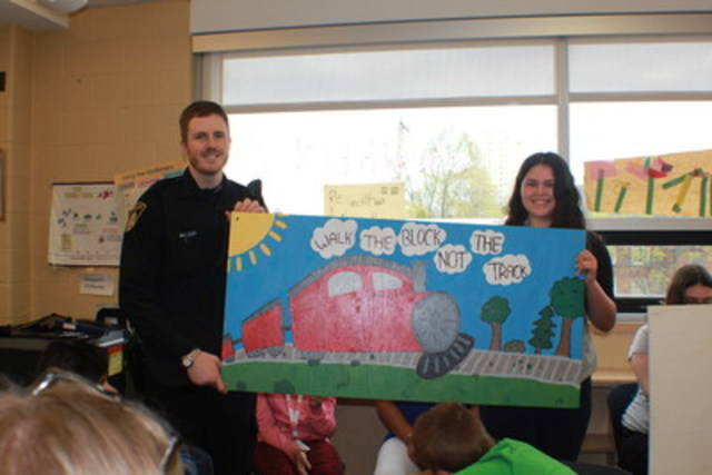 Constable Archdekin and Queen Victoria Elementary School student displaying art work. (CNW Group/Canadian Pacific)