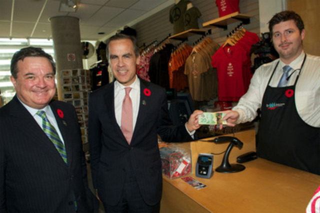 Mark Carney, Governor of the Bank of Canada, buys the Vimy Pin with Canada's new $20 polymer bank note, as the Honourable Jim Flaherty, Minister of Finance, looks on. The transaction, at the Canadian War Museum's gift boutique, followed the ceremony issuing the new $20 note into circulation. (CNW Group/Bank of Canada)