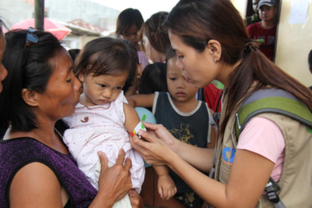 An Action Against Hunger nutrition expert measures children for malnutrition in disaster-struck Panay Island, Philippines on Thursday (CNW Group/Action Against Hunger (AAH))