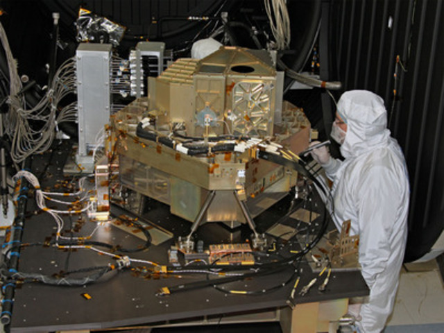 A COM DEV employee completes final work on the Fine Guidance Sensor (FGS) and Near-Infrared Imager and Slitless Spectrograph (NIRISS), in preparation for shipping the instrument to NASA for integration onto the James Webb Space Telescope. Photo courtesy of the Canadian Space Agency (CSA) and the Communications Research Centre (CRC). (CNW Group/Com Dev International Ltd.)