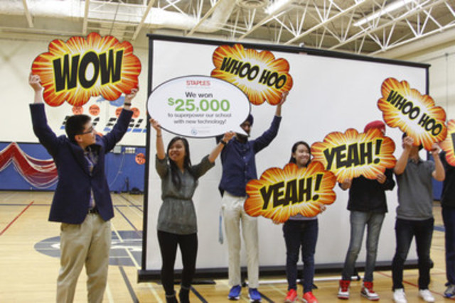 R.E. Mountain Secondary School students hold up signs announcing their school as winners in the 2016 Staples Canada Superpower your School Contest. The school won $25,000 worth of technology for their eco efforts. (CNW Group/Staples Canada Inc.)
