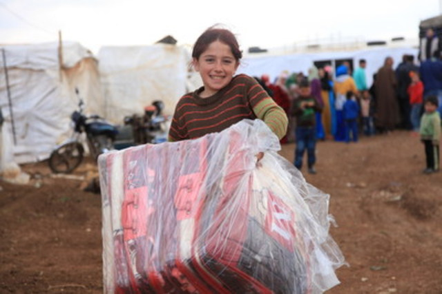 Syrian girl at an informal refugee settlement in Lebanon holds the blankets she and her siblings were provided by World Vision. The Help the Syrian Crisis donation from the World Vision Gift Catalogue provides a present Canadians can give to loved ones concerned about recent global events. (CNW Group/World Vision Canada)