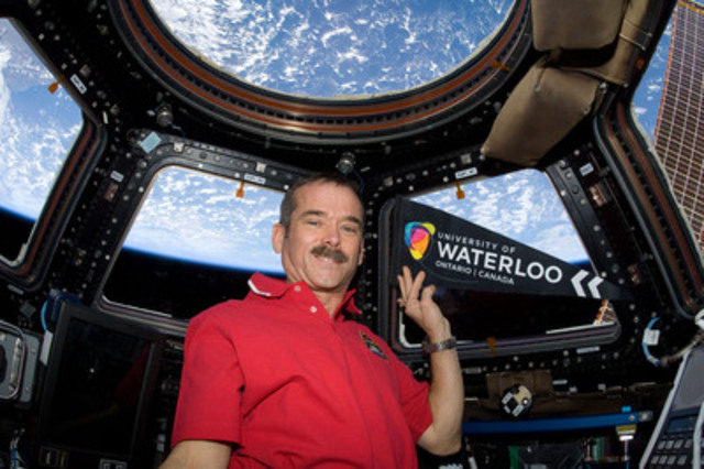 Canadian Space Agency Astronaut Chris Hadfield is shown aboard the International Space Station with a University of Waterloo pennant. Hadfield is participating in university research during the mission and will connect with the university via a space-to-Earth downlink on Friday, Feb. 15. -Photo: NASA/CSA (CNW Group/University of Waterloo)