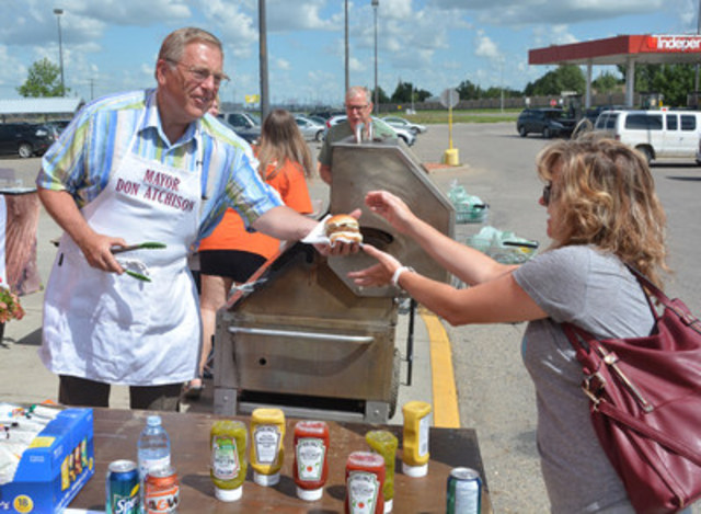 Saskatoon mayor Don Atchison serves up a hamburger on a sunny day in Saskatoon, Saturday July 16, 2016 as a guest at a BBQ hosted by World Vision as part of their Campaign for Children. The campaign celebrates the difference people in Saskatchewan are making in children's lives around the world, and is raising awareness of the organization's work. (CNW Group/World Vision Canada)
