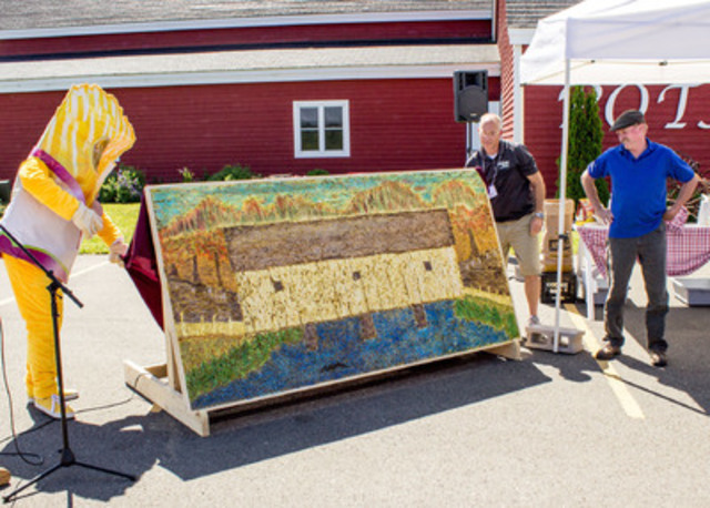 Crispy, the Town Mascot unveils the finished art with the help of Charles Walker from the Town of Florenceville-Bristol and artist, Kerry O'Toole. (CNW Group/Town of Florenceville-Bristol)