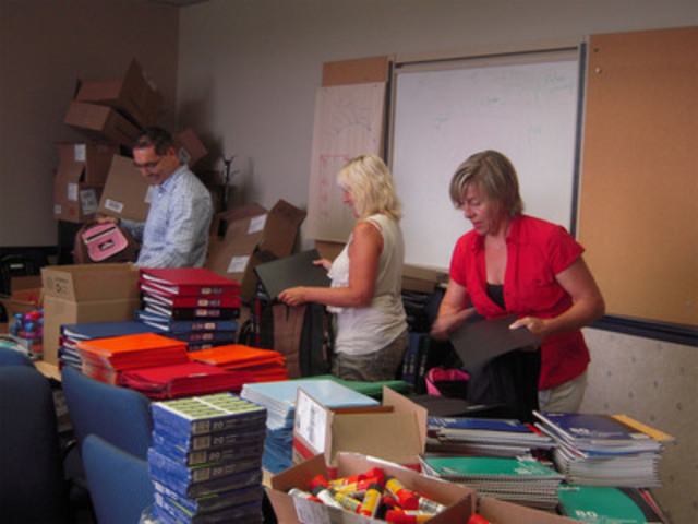 Alain Cloutier (left), Johanne Forcier (middle) and Danielle Pilote (right), Bell Aliant employees, prepare backpacks, which will be distributed throughout Quebec. (CNW Group/BELL ALIANT INC.)