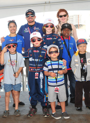 IndyCar driver Alex Tagliani celebrates Fan Friday with children from Make-A-Wish Canada. On Fan Friday the Honda Indy Toronto is free for fans who make a donation to Make-A-Wish® Canada. Fan Friday is made possible through the generosity of fans and the Ontario Honda Dealers Association. (CNW Group/Honda Canada Inc.)