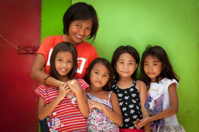 Mai, a World Vision aid worker, with Filipino children in the Estancia community. This region of the Philippines was severely hit by Typhoon Haiyan in 2013, but thanks to child sponsorship World Vision was able to respond quickly to help children and families in the region recover. (CNW Group/World Vision Canada)