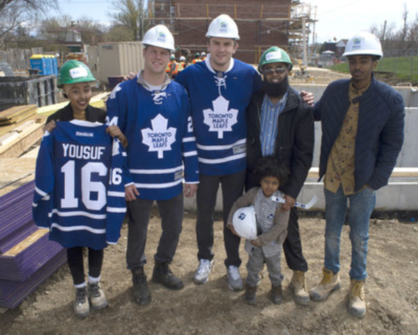 Toronto Maple Leaf players Peter Holland and James van Riemsdyk pose with the Yousuf family after the team announced a new partnership with Habitat for Humanity GTA as a Title Home Sponsor of the Yousuf Family home on Birchmount Road in Toronto. (CNW Group/Habitat for Humanity GTA)