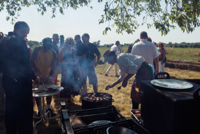 Guests gather around as Chef Jamie Kennedy barbeques for the farm-to-table dinner at Pleasant Valley Farm (CNW ...