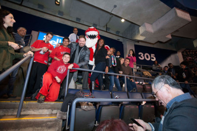 Drew Green, CEO and Founder of SHOP.CA and Stripes, Toronto Raptors mascot enjoy the game with kids from his former childhood school, St. Margaret's Public School (CNW Group/SHOP.CA)