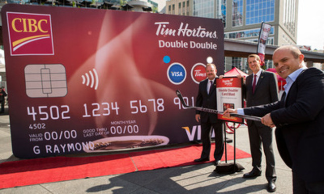Former Toronto hockey star Tie Domi shows off his skills at the official launch of the CIBC Tim Hortons Double Double Visa Card. Looking on are David Clanachan from Tim Hortons and CIBC's David Williamson. (CNW Group/CIBC)