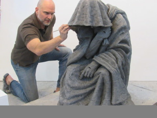 "Tim Schmalz works on ""When I Was a Stranger,"" a sculpture that invites pedestrians to sit on bronzed ..."