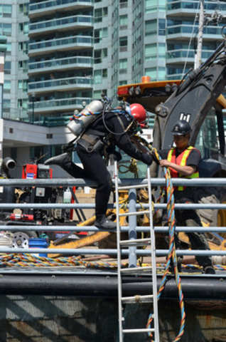 As part of Toronto Hydro's work on Waterfront Toronto's revitalization project, a diver prepares to get wet and attempt to plug openings on the dock wall in front of Captain John's boat. The water table in this area is high, pushing water into newly dug trenches. This unique solution in the urban core will speed up the process of relocating and adding more cable to accommodate new customers. (CNW Group/Toronto Hydro Corporation)