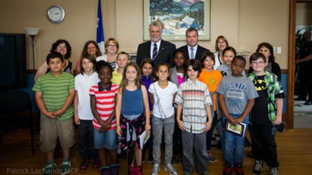 Le premier ministre Philippe Couillard en compagnie des représentants de la Commission scolaire de Montréal et de l'école Baril avec un groupe d'élèves. (Groupe CNW/Cabinet du ministre de l'Éducation, du Loisir et du Sport)