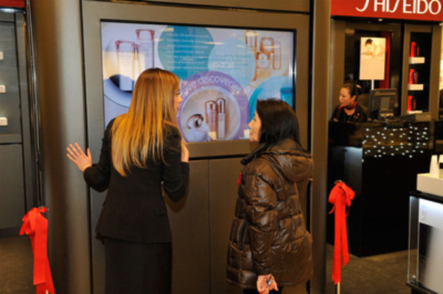 Erika Hogerwaard (Shiseido) demonstrates the Shiseido Discovery Centre multi-touch screen to a customer during the counter launch gala on January 19, 2012. (CNW Group/Shiseido Canada Inc.)