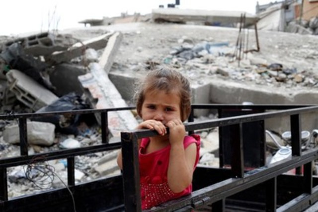 A young girl holds a railing outside her family's partially destroyed home in Gaza City. She is among 60 children and 20 adults from the same family living in the house, which was hit during an air strike a year ago. The rubble and debris from the dwelling - visible behind her - serves as the children's playground. © UNICEF/UNI188295/El Baba (CNW Group/UNICEF Canada)