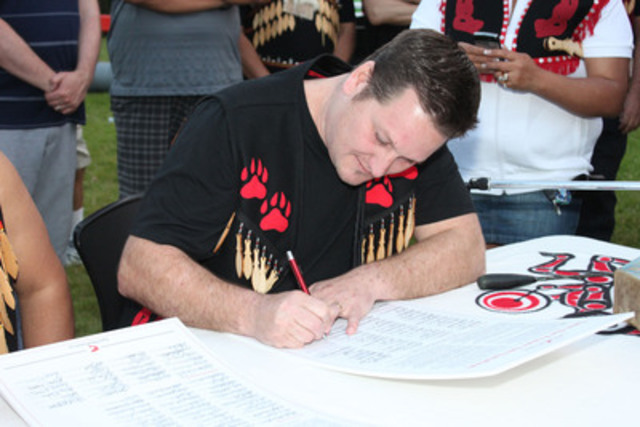 Chief Justin George, Qut-same, of Tsleil-Waututh Nation, signs the Save the Fraser Declaration opposing tar sands pipelines through First Nations territories. Photo by James Maclennan (CNW Group/Tsleil-Waututh Nation)