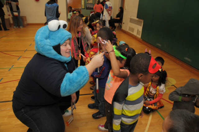 Pictured is Sylvania Canada's Colleen Applebaugh dressed as a certain cookie monster handing out LED lite sticks to kindergarten children at Stanley Public School in the Jane Sheppard area of Toronto. (CNW Group/Sylvania Canada)