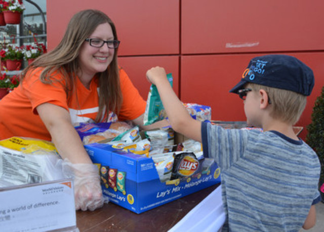 Ashly Yaknovich, a volunteer for World Vision, serves up bags of chips on a sunny day in Saskatoon, Saturday, ...