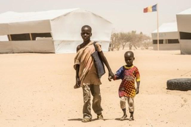 En avril 2015, Bello, âgé de 12 ans, revient de l'école à pied en compagnie de son jeune frère, Alei Kolo, dans le camp de Dar es Salam, au Tchad. Leur famille fait partie des 4 900 personnes réfugiées du Nigeria qui se trouvent dans le camp, où l''UNICEF a mis en place 16 espaces d''apprentissage temporaires. L''organisme a aussi procuré du matériel pédagogique et des fournitures scolaires, ainsi que d'autres outils éducatifs, dont bénéficient les enfants dans le camp. (Groupe CNW/UNICEF Canada)