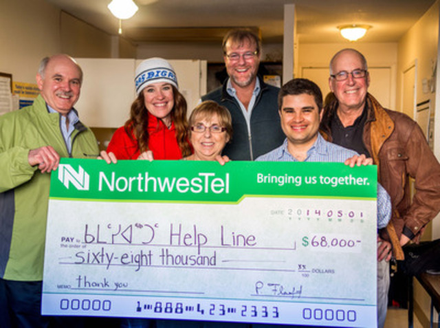 Northwestel President Paul Flaherty and Bell Let's Talk spokesperson Clara Hughes make a donation to Sheila Levy, John Vander Velde, Eduardo Viega, and Lawrence Levy of Nunavut Kamatisiaqtut Help Line as Clara's Big Ride for Bell Let's Talk visits Iqaluit (CNW Group/Bell Canada)