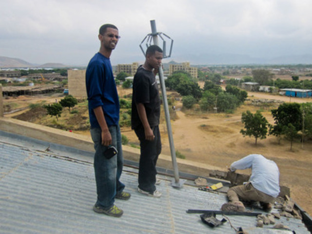 With Dire Dawa University in the background, Ethiopian diaspora volunteer Yared Ayele (left), stands with colleague Bisrat Ayelew during the installation of a network access point antenna. (CNW Group/CUSO International)